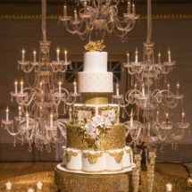 white and gold wedding cake, chandelier wall