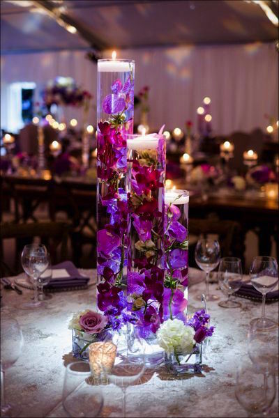 cylinder vases filled with flowers, candles, orchids